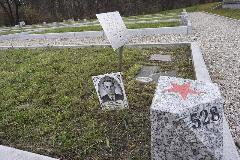 Родственники ставят таблички на братских могилах.