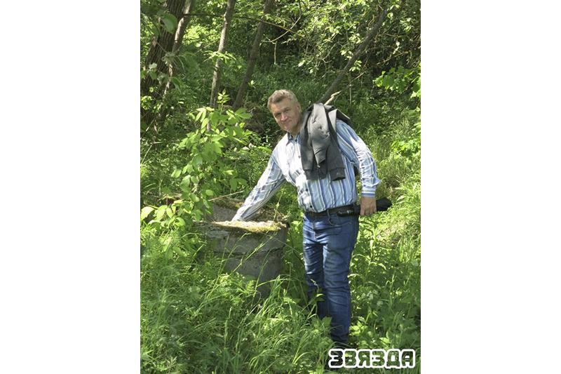 Леанід Платоненка паказвае адкрытыя небяспечныя калодзежы ў Пячэрскім лесе.