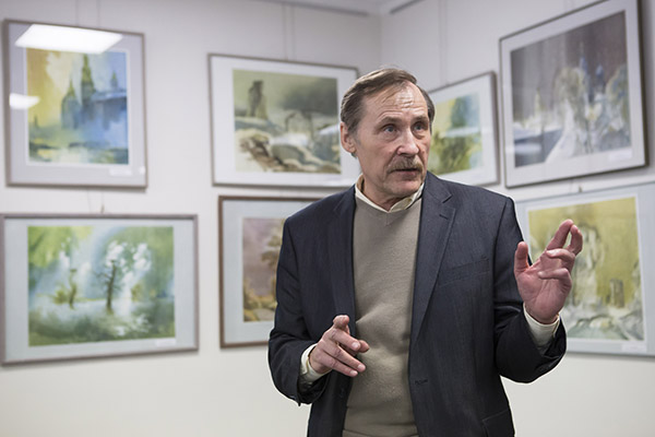 Фёдар Кісялёў падчас адкрыцця выстаўкі на фоне сваіх акварэляў, прысвечаных знакавым беларускім мясцінам.