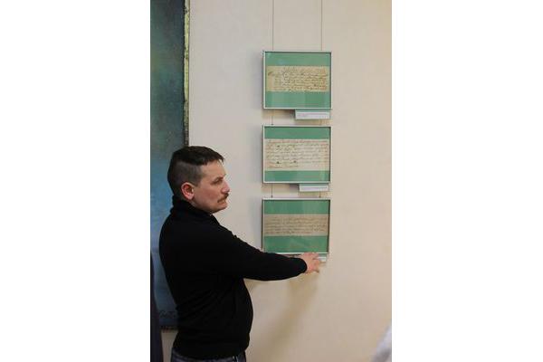 Даследчык Зміцер Юркевіч паказвае копіі метрык з запісамі аб хрышчэнні і шлюбе.