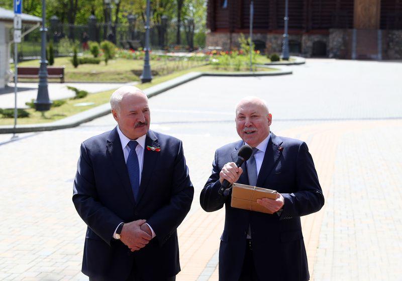 Аляксандр Лукашэнка прымае кнігу ад Дзмітрыя Мезенцава. Фота БЕЛТА