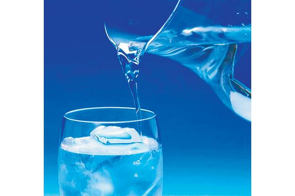 Вода из графина наливается в стакан со льдом