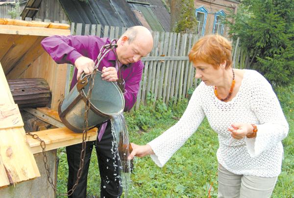 Мужчина наливает воду из колодца в бутылку