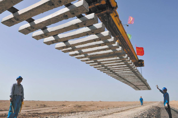Workers direct a crane to lay a segment of tracks on the Kumul-Lop Nor line's railway bed in Lop Nor